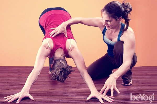 yoga teacher giving adjustments