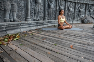Asian young woman doing hatha yoga in abandoned temple.