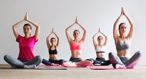 Group of women doing yoga in a fitness gym. Sport group practicing yoga.