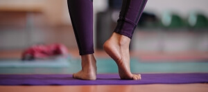 woman standing barefoot at yoga class. no face