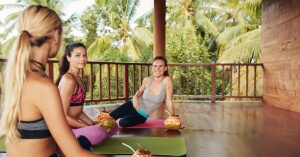 Women in yoga class taking break. Three beautiful girls relaxing with coconut juice and chatting after yoga session. Group of women relaxing after a long yoga class.