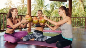 Shot of group of young female friends toasting green coconuts at yoga class. Group of fitness female having coconut juice during break.