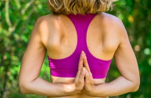 A woman with her hands at her back in a tree-like yoga pose