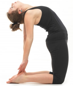 young attractive woman in back reversed yoga pose, side view, dressed in black on white background