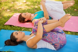 Cute female friends doing some stretching and getting ready for their yoga practice