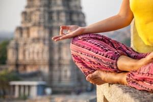 Woman doing meditation near Virupaksha temple in Hampi, Karnataka, India