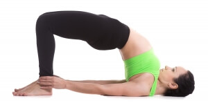 Beautiful sporty girl doing yoga workout, standing in bridge pose, dvi pada pithasana, setu bandhasana, set exercises for strengthening back and shoulders muscles