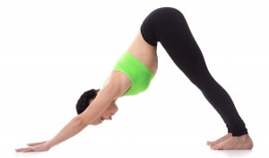 Sporty girl on white background stretching in downward-facing dog yoga pose, adho mukha svanasana, asana from Surya Namaskar sequence, Sun Salutation complex