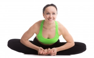Cheerful smiling sporty girl doing yoga practice, sitting in bound angle posture, baddha konasana, cobbler pose