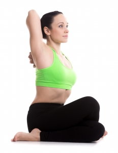 Sporty girl doing yoga workout, sitting in Gomukhasana, Cow face pose, asana for stretching triceps, shoulders, hips and thighs, side view