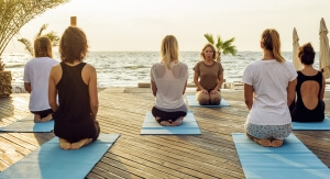 group of young females practicing yoga on the seaside during the sunris