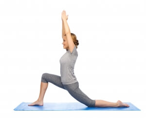 fitness, sport, people and healthy lifestyle concept - happy woman making yoga in low lunge pose on mat