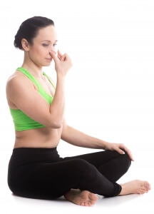 Calm beautiful girl practicing hatha yoga nadi shodhana pranayama (Alternate Nostril Breathing), sitting cross-legged in Easy Pose, Sukhasana, meditation, Vishnu mudra, copy space