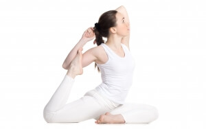 Sporty beautiful young woman in white sportswear sitting in variation of One Legged King Pigeon Pose - Eka Pada Rajakapotasana, studio full length profile view, isolated