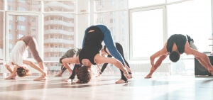 Group of people stretching and doing yoga exercises in studio